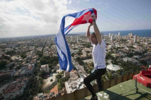 """See more French Spiderman photos on Flickr Alain Robert of France, who is known as """"Spiderman"""", celebrates with the Cuban national flag on the roof of the Habana Libre hotel in Havana February 4, 2013. Robert, who scales buildings all over the world without safety equipment, successfully climbed the hotel which is 126 metres (413 feet) high. REUTERS/Ramon Espinosa/Pool"""