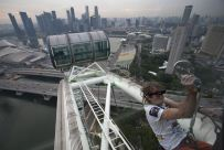 """French climber Alain Robert, also known as """"Spiderman"""", scales the 165-metre-high (541-feet) Singapore Flyer observation wheel in Singapore November 5, 2010. REUTERS/Vivek Prakash"""