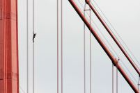 """French daredevil climber Alain Robert, known as """"Spiderman"""", climbs up the April 25 bridge over the Tagus river in Lisbon August 6, 2007. REUTERS/Marcos Borga"""