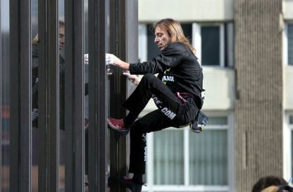 """French """"Spiderman"""" Alain Robert climbs up the Mercuriales towers in Bagnolet, eastern Paris March 15, 2006. REUTERS/Charles Platiau"""
