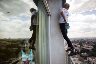 "Alain Robert of France, who is known as ""Spiderman"", climbs up the Habana Libre hotel as a youth looks out a window in Havana February 4, 2013. Robert, who scales buildings all over the world without safety equipment, successfully climbed the hotel which is 126 metres (413 feet) high. REUTERS/Ramon Espinosa/Pool"