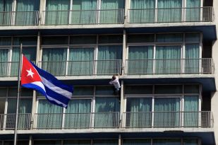 """Alain Robert of France, who is known as """"Spiderman"""", climbs up the Habana Libre hotel in Havana February 4, 2013. Robert, who scales buildings all over the world without safety equipment, successfully climbed the hotel which is 126 metres (413 feet) high. Also seen is the Cuban national flag. REUTERS/Enrique De La Osa"""