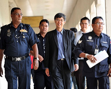 Tian Chua (center) being escorted by police officers as he was led out of the courtroom this morning. Pic: Faisol Mustafa/MD