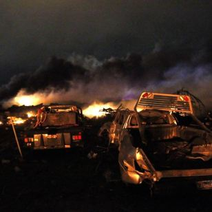 Vehicles are seen near the remains of a fertilizer plant burning after an explosion at the plant in the town of West, near Waco, Texas early April 18, 2013. The deadly explosion ripped through the fertilizer plant late on Wednesday, injuring more than 100 people, leveling dozens of homes and damaging other buildings including a school and nursing home, authorities said. REUTERS/Mike Stone