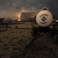 A chemical trailer sits among the remains of a fertilizer plant burning after an explosion at the plant in the town of West, near Waco, Texas early April 18, 2013. The deadly explosion ripped through the fertilizer plant late on Wednesday, injuring more than 100 people, leveling dozens of homes and damaging other buildings including a school and nursing home, authorities said. REUTERS/Mike Stone