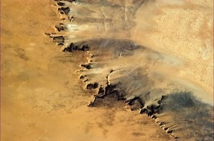 Arid fingers of sand-blasted rock look like they're barely holding on against the hot Saharan wind.