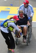 A person who was injured in an explosion near the finish line of the 117th Boston Marathon is taken away from the scene in a wheelchair. (Photo by David L. Ryan/The Boston Globe via Getty Images)