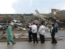People look at the destruction after a huge tornado struck Moore, Oklahoma May 20, 2013. A huge tornado with winds of up to 200 miles per hour devastated the Oklahoma City suburb of Moore on Monday, ripping up at least two elementary schools and a hospital and leaving a wake of tangled wreckage. At least four people were killed, KFOR television said, citing a reporter's eyewitness account, and hospitals said dozens of people were injured as the dangerous storm system threatened as many as 10 U.S. states with more twisters. REUTERS/Gene Blevins (UNITED STATES - Tags: ENVIRONMENT DISASTER)