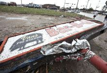 A sign for a local restaurant lies on the ground after a huge tornado struck Moore, Oklahoma, near Oklahoma City, May 20, 2013. A massive tornado tore through the Oklahoma City suburb of Moore on Monday, killing at least 51 people as winds of up to 200 miles per hour (320 kph) flattened entire tracts of homes, two schools and a hospital, leaving a wake of tangled wreckage. REUTERS/Richard Rowe (UNITED STATES - Tags: DISASTER ENVIRONMENT)