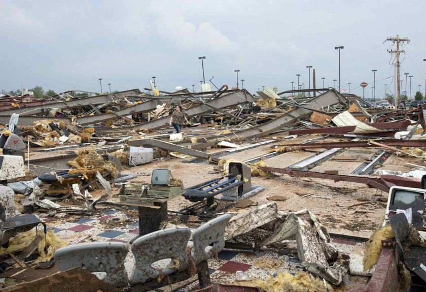 A woman walks through debris after a huge tornado struck Moore, Oklahoma, near Oklahoma City, May 20, 2013. A massive tornado tore through the Oklahoma City suburb of Moore on Monday, killing at least 51 people as winds of up to 200 miles per hour (320 kph) flattened entire tracts of homes, two schools and a hospital, leaving a wake of tangled wreckage. REUTERS/Richard Rowe