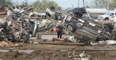 A rescue worker looks for victims in the Moore Hospital parking lot after being hit by a tornado that destroyed buildings and overturned cars in Moore, Oklahoma, near Oklahoma City, May 20, 2013. A huge tornado with winds of up to 200 miles per hour (320 kph) devastated the Oklahoma City suburb of Moore on Monday, ripping up at least two elementary schools and a hospital and leaving a wake of tangled wreckage. At least four people were killed, KFOR television said, citing a reporter's eyewitness account, and hospitals said dozens of people were injured. REUTERS/Gene Blevins (UNITED STATES - Tags: DISASTER ENVIRONMENT)