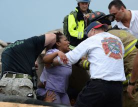 Rescue workers help free one of the 15 people that were trapped at a medical building at the Moore hospital complex after a tornado tore through the area of Moore, Oklahoma May 20, 2013. REUTERS/Gene Blevins (UNITED STATES - Tags: ENVIRONMENT DISASTER TPX IMAGES OF THE DAY