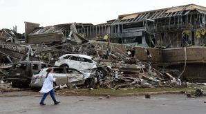 A nurse walks past the destruction at Moore hospital after a huge tornado struck Moore, Oklahoma, near Oklahoma City, May 20, 2013. A huge tornado with winds of up to 200 miles per hour (320 kph) devastated the Oklahoma City suburb of Moore on Monday, ripping up at least two elementary schools and a hospital and leaving a wake of tangled wreckage. REUTERS/Gene Blevins (UNITED STATES - Tags: DISASTER ENVIRONMENT TPX IMAGES OF THE DAY)