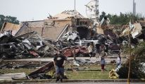 People walk near destroyed buildings and vehicles after a tornado struck Moore, Oklahoma, near Oklahoma City, May 20, 2013. At least 91 people, including 20 children, were feared killed when a 2 mile wide tornado tore through the Oklahoma City suburb of Moore, trapping victims beneath the rubble as one elementary school took a direct hit and another was destroyed. REUTERS/Gene Blevins (UNITED STATES - Tags: ENVIRONMENT DISASTER)