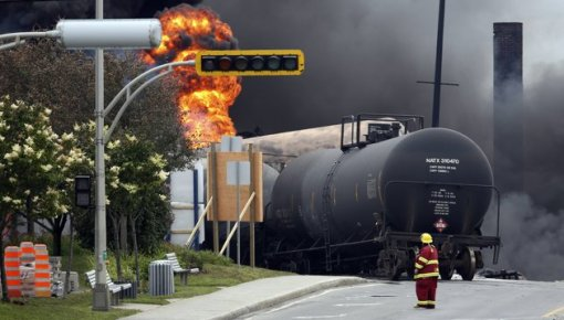 A firefighter walks past a burning train wagon at Lac Megantic, Quebec, July 6, 2013. Several people were missing after four tank cars of petroleum products exploded in the middle of a small town in the Canadian province of Quebec early on Saturday in a fiery blast that destroyed dozens of buildings. REUTERS/Mathieu Belanger (CANADA - Tags: DISASTER SOCIETY) A firefighter walks past the remains of buildings after a train explosion at Lac Megantic, Quebec, July 6, 2013. REUTERS/Mathieu Belanger (CANADA - Tags: DISASTER SOCIETY TPX IMAGES OF THE DAY) A burning train wagon is seen after an explosion at Lac Megantic, Quebec, July 6, 2013. REUTERS/Mathieu Belanger (CANADA - Tags: DISASTER SOCIETY)
