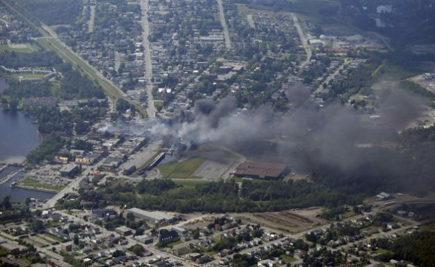 Smoke billows from a fire at the site of a train derailment in Lac Megantic, Quebec in this July 6, 2013 aerial handout photo. Several people were reported missing after four tank cars of petroleum products exploded in the middle of the small town in a fiery blast that destroyed dozens of buildings. REUTERS/Surete du Quebec/Handout (CANADA - Tags: TRANSPORT DISASTER) ATTENTION EDITORS - THIS IMAGE WAS PROVIDED BY A THIRD PARTY. FOR EDITORIAL USE ONLY. NOT FOR SALE FOR MARKETING OR ADVERTISING CAMPAIGNS. THIS PICTURE IS DISTRIBUTED EXACTLY AS RECEIVED BY REUTERS, AS A SERVICE TO CLIENTS