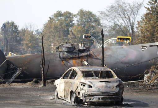 A burnt out vehicle sits near the wreckage of a train car after a train derailment in Lac-Megantic, Quebec, July 7, 2013. A driverless freight train carrying tankers of petroleum products derailed at high speed and exploded into a giant fireball in the middle of the small Canadian town of Lac-Megantic early on Saturday, destroying dozens of buildings and leaving an unknown number of people feared missing. REUTERS/Christinne Muschi (CANADA - Tags: DISASTER TRANSPORT)