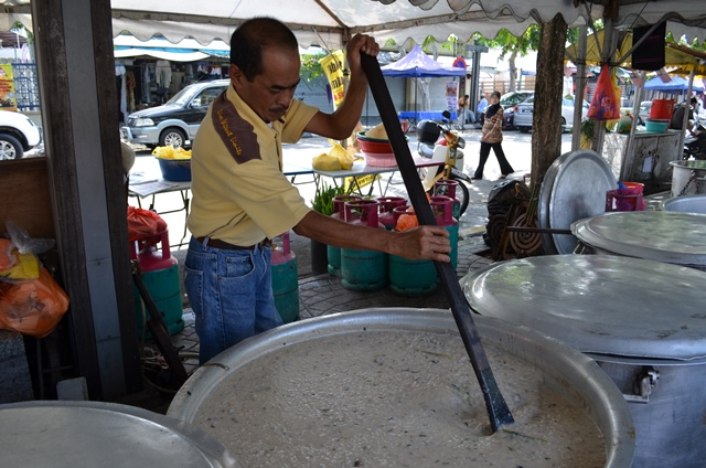 Aunty Sham's brother is stirring a huge pot of bubur lambuk.
