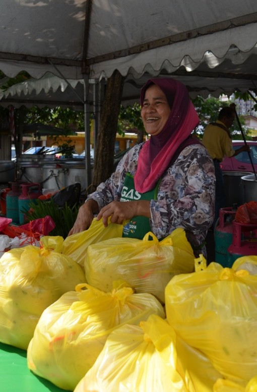 Aunty Sham packing her bubur lambuk that were ordered by her customers.