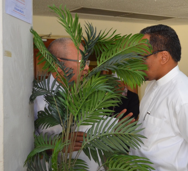 Ibrahim Ali and Ustaz Nasharudin Mat Isa having a secret discussion hiding behind a plant.