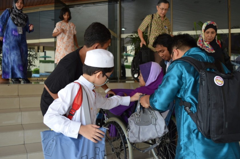 Mat Som is carried on her wheelchair to go to the car.