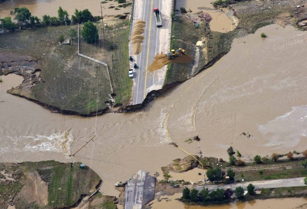 A road crew works on a stretch of highway washed out by flooding along the South Platte River in Weld County, Colorado near Greeley, Saturday, Sept. 14, 2013. Hundreds of roads in the area have been damaged or destroyed by the floodwaters that have affected parts of a 4,500-square-mile (11,655-square-kilometer) area — an area the size of the U.S. state of Connecticut. (AP Photo/John Wark)