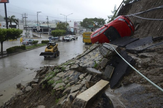 A car lies on its side after a portion of a hill collapsed due to heavy rains in the Pacific resort city of Acapulco, Mexico, Sunday, Sept. 15, 2013. Flooding and landslides unleashed by Hurricane Ingrid and Tropical Storm Manuel have claimed at least a dozen lives in Mexico and sparked the evacuations of thousands of people even before the weather systems had made landfall on the country's east and west coasts. (AP Photo/Bernandino Hernandez)