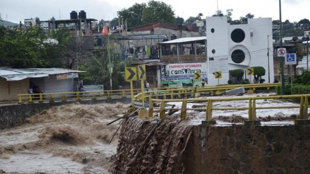 Floodwaters rage past an urban area after the Huacapa River overflowed due to heavy rains caused by Tropical Storm Manuel in Chilpancingo, Mexico. (Image: AP Photo/Alejandrino Gonzalez)
