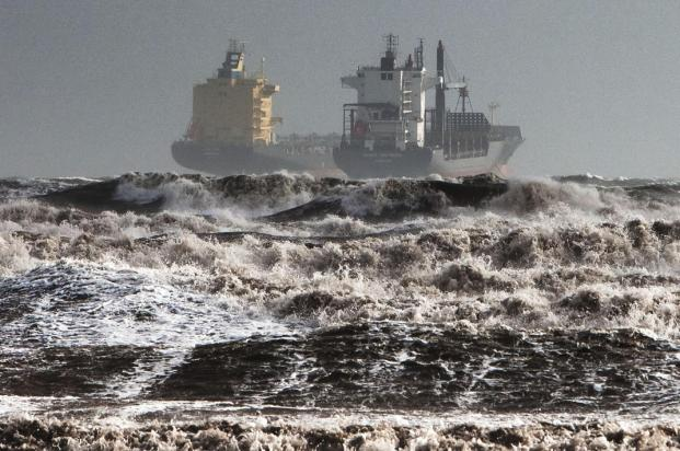 Two tankers are battered by gale winds while at the roadstead in the rough waters of the Gulf of Cagliari, Sardinia, Monday, Nov. 18, 2013. A violent rainstorm that flooded entire parts of the Mediterranean island of Sardinia has led to the deaths of at least nine people. Bridges were felled by swollen rivers and water levels reached 3 metres (yards) in some places. (AP Photo/Max Solinas)