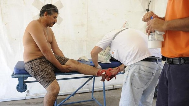 A man is treated after he was bit by a palometa, a type of piranha, while wading in the Parana River in Rosario, Argentina. Photo: AP Read more: http://www.smh.com.au/world/70-hurt-in-piranha-attack-in-argentina-20131227-hv6xx.html#ixzz2ogFaxWpg