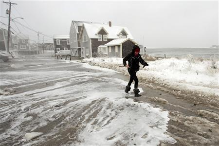 A woman runs from the surf as waves crash into houses on Lighthouse Road during a winter nor'easter snow storm in Scituate, Massachusetts January 3, 2014. REUTERS/Dominick Reuter.