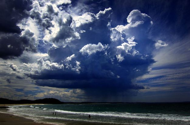 An ominous storm cloud hovers above swimmers near Mollymook Beach, south of Sydney. The storm generated heavy rain and high gusts of wind. (REUTERS/David Gray)