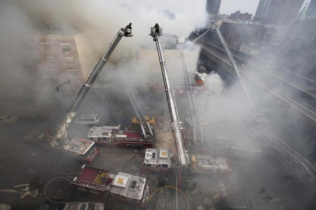 Firefighters respond to a fire on 116th Street in Harlem after a building exploded in huge flames and billowing black smoke, March 12, 2014, in New York. (AP Photo/John Minchillo)