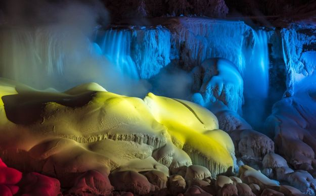 The partially frozen Falls are illuminated by multicoloured lights. (Reuters)