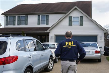 An FBI agent enters the family home of a suspect after a series of knife attacks at at Franklin Regional High School in Murrysville, Pennsylvania April 9, 2014. REUTERS/Shannon Stapleton