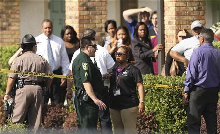 Parents wait behind as police consult after several children were injured after being struck by a vehicle at a KinderCare Learning Center in Winter Park, Florida April 9, 2014. REUTERS/Stephen M. Dowell/Orlando Sentinel