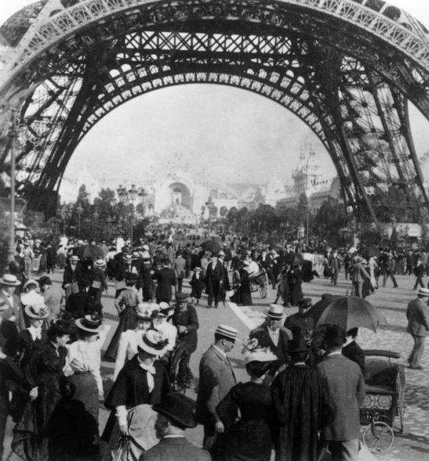1900: Visitors to the World Exposition walking under the Eiffel Tower, with a view of the Chateau d'Eau in the background, Paris, France.  (Photo by Hulton Archive/Getty Images)