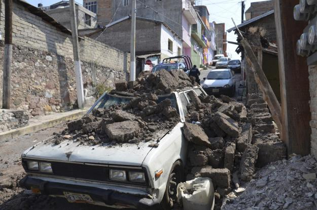 A parked car suffered damage when a adobe wall collapsed on it after a strong earthquake shook Chilpancingo, Mexico, Friday morning, April 18, 2014. A powerful magnitude-7.2 earthquake shook central and southern Mexico but there were no early reports of major damage or casualties. (AP Photo/Alejandrino Gonzalez).