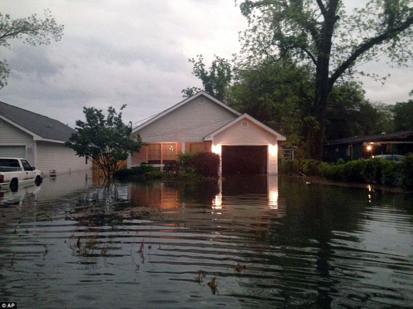 Running to safety: In this photo provided by Kyle Smith, floodwaters surround Smith's home in Pensacola on Wednesday. Smith had to evacuate his home with his 18-month-old son Tuesday night after severe weather hit the Florida Panhandle, causing widespread flooding. (DailyMail)