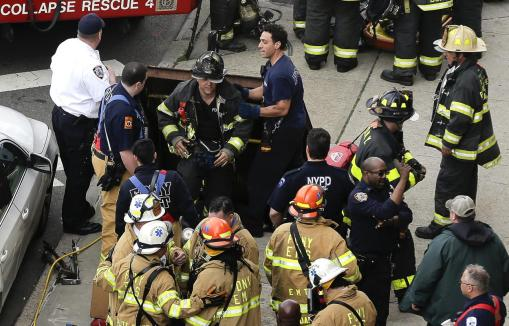 New York City firefighters emerge from a hatch in the sidewalk at 60th Street and Broadway after evacuating passengers from a subway train that derailed in the Queens borough of New York, Friday, May 2, 2014.(AP Photo/Julie Jacobson)