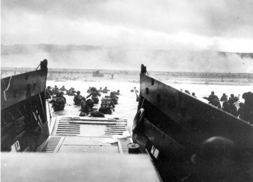 Under heavy German machine gun fire, American infantrymen wade ashore off the ramp of a Coast Guard landing craft on June 6, 1944. (PA)