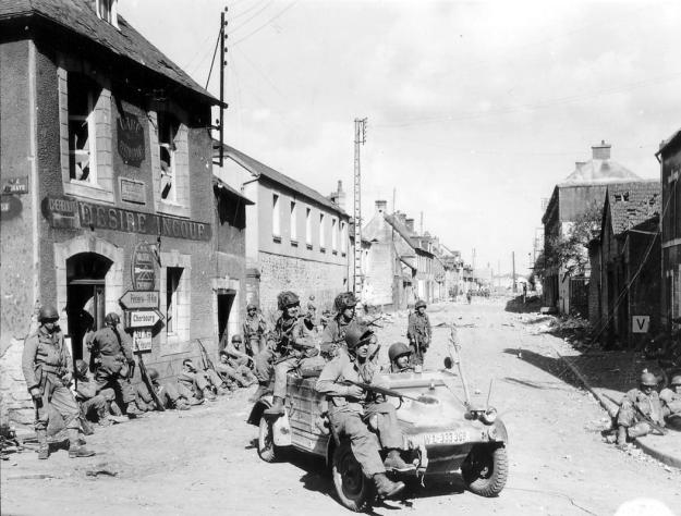 U.S. Army paratroopers of the 101st Airborne Division drive a captured German Kubelwagen on D-Day at the junction of Rue Holgate and RN13 in Carentan, France, June 6, 1944. (REUTERS/US National Archives)