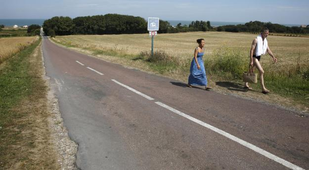 A couple walk inland from the former D-Day landing zone of Gold Beach where British forces came ashore in 1944, in Ver-sur-Mer, France August 23, 2013. (REUTERS/Chris Helgren)