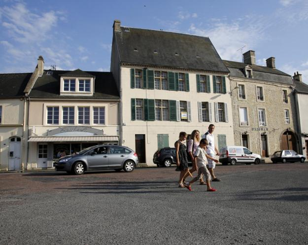 Tourists walk across the main square of Place Du Marche near the former D-Day landing zone of Omaha Beach, in Trevieres, France August 23, 2013. (REUTERS/Chris Helgren)