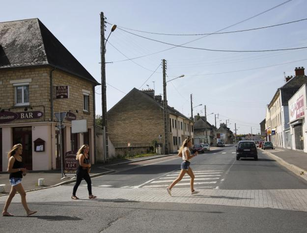 Girls run across the street at the junction of Rue Holgate and RN13 in the Normandy town of Carentan, France, June 21, 2013. (REUTERS/Chris Helgren)