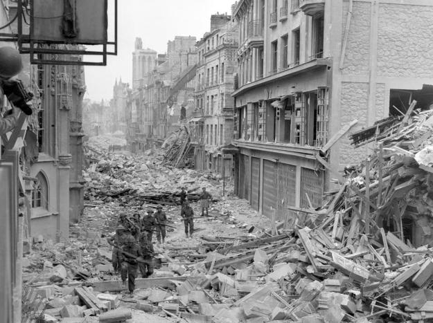 Canadian troops patrol along the destroyed Rue Saint-Pierre after German forces were dislodged from Caen in July 1944. British and Canadian troops battled reinforced German troops holding the area around Caen for about two months following the D-Day landings in Normandy. (REUTERS/US National Archives)