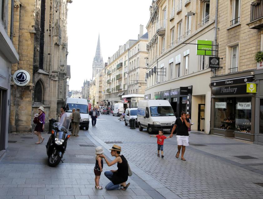 Shoppers walk along the rebuilt Rue Saint-Pierre, which was destroyed following the D-Day landings, in Caen August 23, 2013. British and Canadian troops battled reinforced German troops holding the area around Caen for about two months following the D-Day landings in Normandy in 1944. (REUTERS/Chris Helgren)