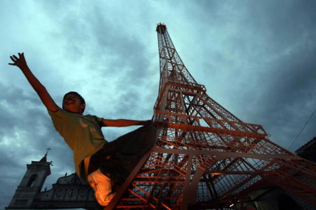 HONDURAS: A boy plays on a replica of the Eiffel Tower at Los Dolores square in Tegucigalpa July 18, 2010. The French embassy in Honduras donated the 6 metre (20 feet) replica to the city of Tegucigalpa to commemorate France's 221 years of independence on Sunday. The replica was the first in Latin America and the 18th in the world, according to embassy officials. (REUTERS/Edgard Garrido)