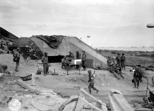 U.S. Army troops congregate around a signal post used by engineers on the site of a captured German bunker overlooking Omaha Beach after the D-Day landings near Saint Laurent sur Mer June 7, 1944. (REUTERS/US National Archives)