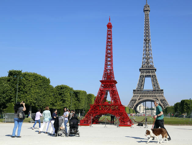 FRANCE: People stop to observe a replica of the Eiffel Tower built with red bistro chairs to mark the 125th anniversary of the Fermob company's bistro chairs in Paris June 24, 2014. Like the Eiffel Tower, the famous bistro chairs celebrate their 125th anniversary this year. (REUTERS/John Schults)